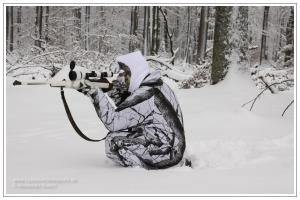 Getarnter Jäger im Winterwald