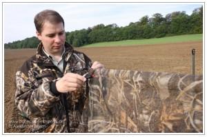 Jäger beim Abspannen des durchsichtigen Nylontarnnetzes im Muster Max-4 mit Hilfe von Klemmen