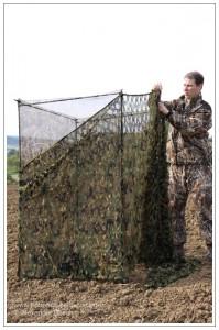 Jäger verkleidet die Rückwand und die Seitenwände eines Tarnschirmes mit blickdichtem Tarnnetz