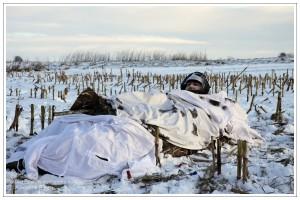 Jäger in einem gut getarnten Layout Blind auf verschneitem Maisstoppel