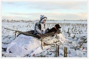 Jäger mit Wachtelhund im Layoutblind auf verschneitem Maisstoppel