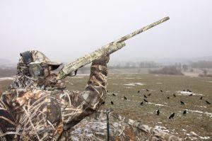 Jäger mit Tarnanzug in Realtree Max-4® bei der Krähenjagd am freundlichen Lockbild aus beflockten Lockkrähen