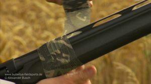 Jäger umwickelt Flinte mit Stretch-Tarnband