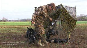 Jäger mit erlegten Krähen am Tarnstand