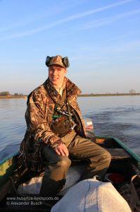 Jäger steuert Boot mit Außenborder