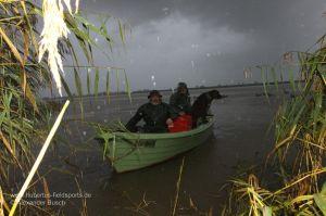 Jäger im Boot bei Regen