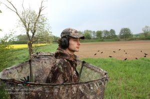 Jäger schaut über den Rand eines Tarnstandes bei der Krähenjagd