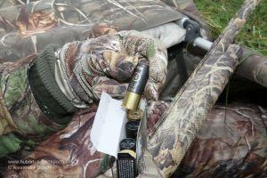 Jäger in Tarnkleidung zeigt Schrotpatrone