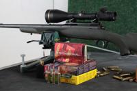 Remington-, Hornady-, Barnes- und RWS-Munition, arrangiert vor Savage-Büchse im Einschießbock.