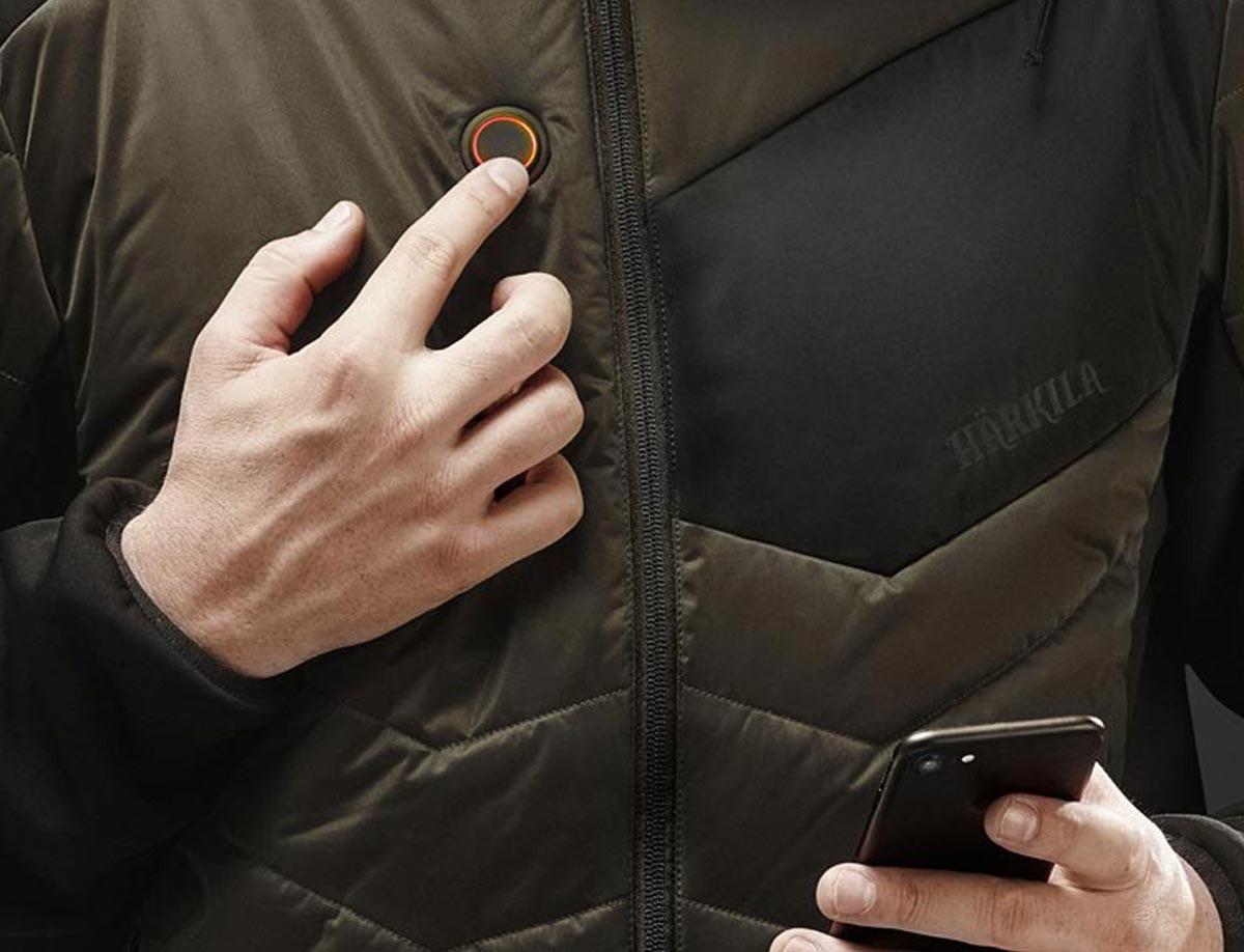 Detailansicht einer Jagdjacke oder Heizweste mit Härkila-HEAT-Control-Funktion: Einstell-Knopf, sowie Smartphone.