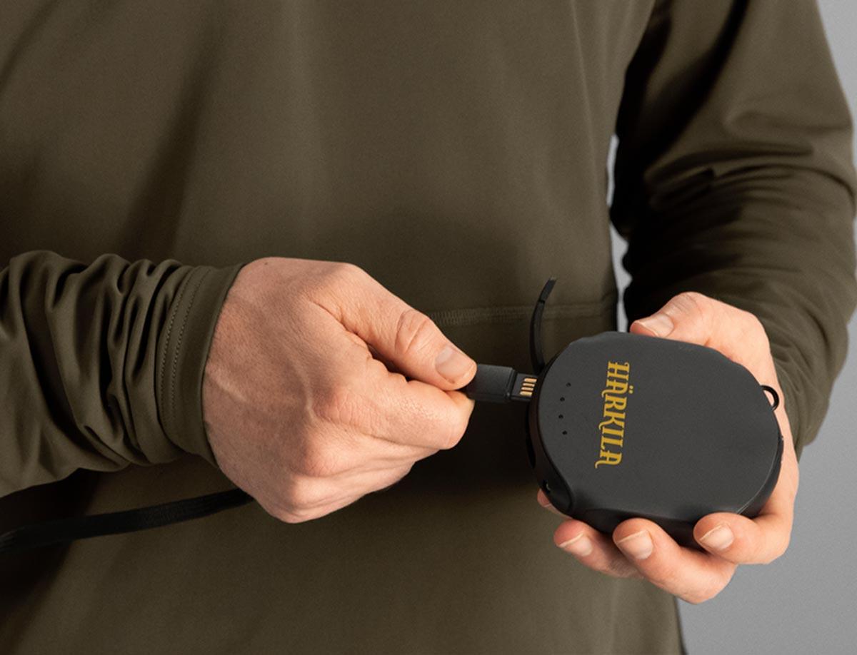 Foto, auf dem der USB-Anschluss eines Härkila-HEAT-Control-Produktes mit einer Powerbank gekoppelt werden soll.