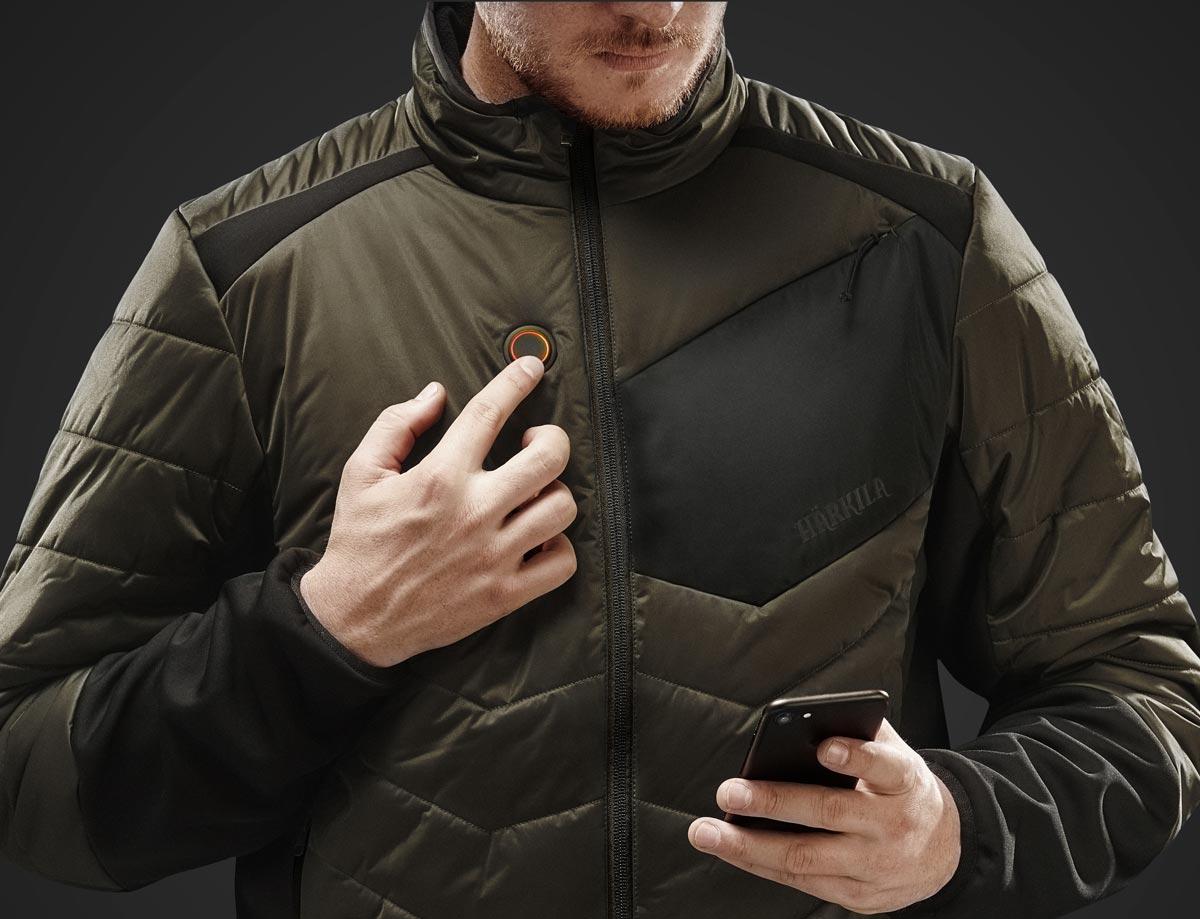 Detailansicht einer Härkila-HEAT-Control-Heizjacke mit Einstelltaste und Smartphone.
