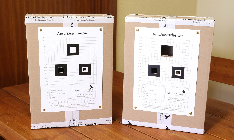 Zwei Kartons, präpariert um ein Wärmebildvorsatzgerät an einer Waffe zu kalibrieren. Mit Klebeband abgedichtet und Anschussscheibe mit Öffnungen an der Vorderseite.